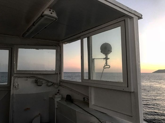Ferryboat Transportation Ship Ferryboat Window No People Nature Architecture Built Structure Sky Indoors  Glass - Material Lighting Equipment Day Scenics - Nature Sea Sunlight Transparent Water Sunset Land Beach Electric Lamp