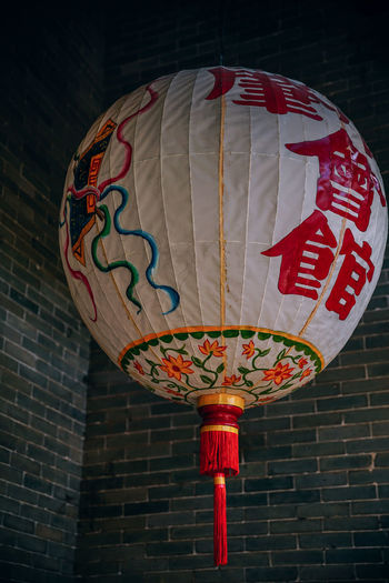 Low angle view of lantern hanging against wall
