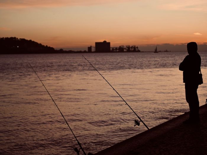 Sunset Sky Water One Person Fishing Activity Silhouette Orange Color Sea Real People Standing Fishing Rod Rear View Men Nature Rod Beauty In Nature Leisure Activity Outdoors