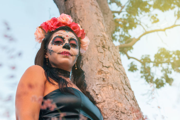 Low angle view of woman with halloween make-up standing by tree trunk