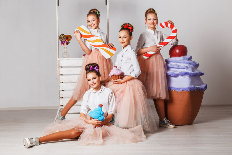 Beautiful teenage model girls in pink tutu or tulle skirts with macaroons, fancy cakes and sweets in studio on white background Advertising Models Agency Beautiful People Cheerful Child Females Friendship Front View Group Of People Indoors  Selling Sitting Smiling Stage Costume Sweeet Togetherness