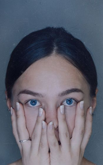 Close-up portrait of young woman against gray background