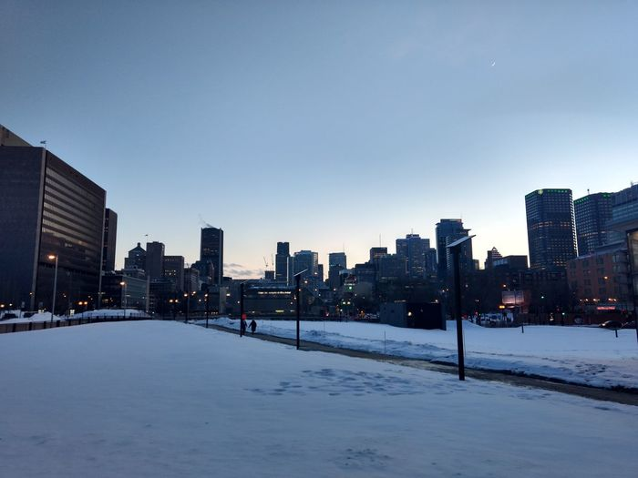 Snow covered buildings in city against sky