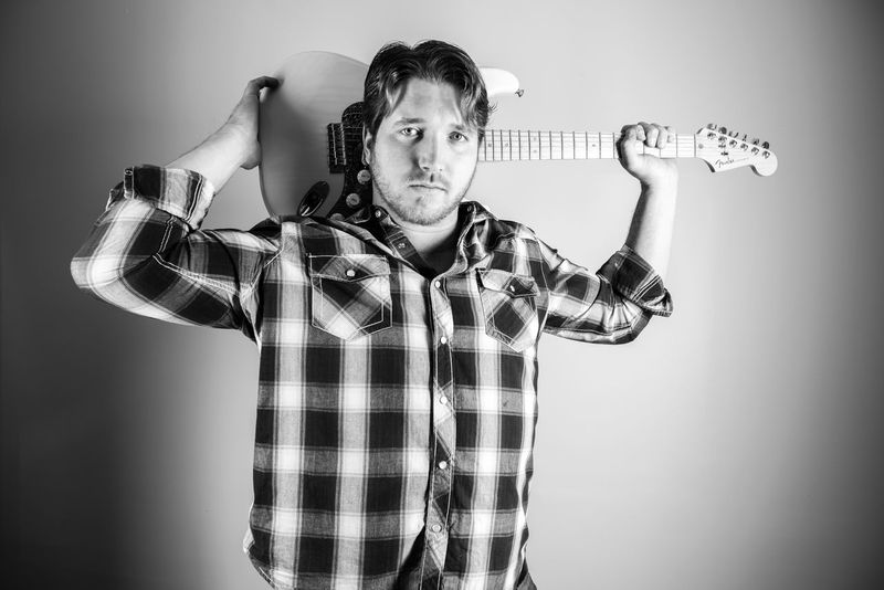 Young man in checked shirt with his guitar over his shoulder posing in studio. Black and White Blackandwhite Casual Clothing Country Music Front View Guitar Indoors  Leisure Activity Lifestyles Looking At Camera Music Musician Musicianlife Person Plaid Shirt  Portrait Smiling Standing Studio Studio Shot Three Quarter Length Young Adult Young Men