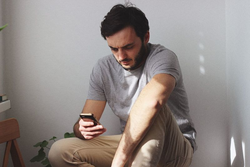 EyeEm Selects Wireless Technology Mobile Phone Young Adult Technology Young Men Smart Phone Connection Real People One Person Portable Information Device Communication Looking Wall - Building Feature Holding Using Phone Casual Clothing Telephone Lifestyles Indoors