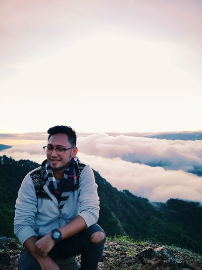 Young Man Wearing Eyeglasses Crouching On Mountain Against Sky During Sunset