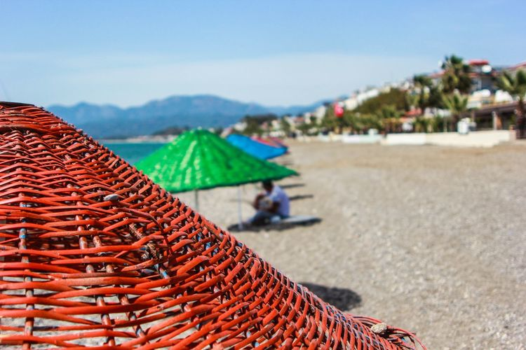 Close-Up Of Orange Wicker Parasol At Beach Against Sky