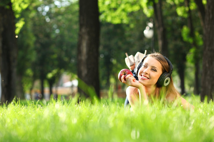 Woman with headphones listening music on the grass Plant Grass Women Young Adult Tree One Person Beauty Nature Land Adult Green Color Young Women Leisure Activity Hair Portrait Selective Focus Lifestyles Day Beautiful Woman Outdoors Fashion Hairstyle Springtime
