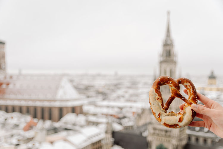 Close-up of hand holding pretzel against buildings in city munich