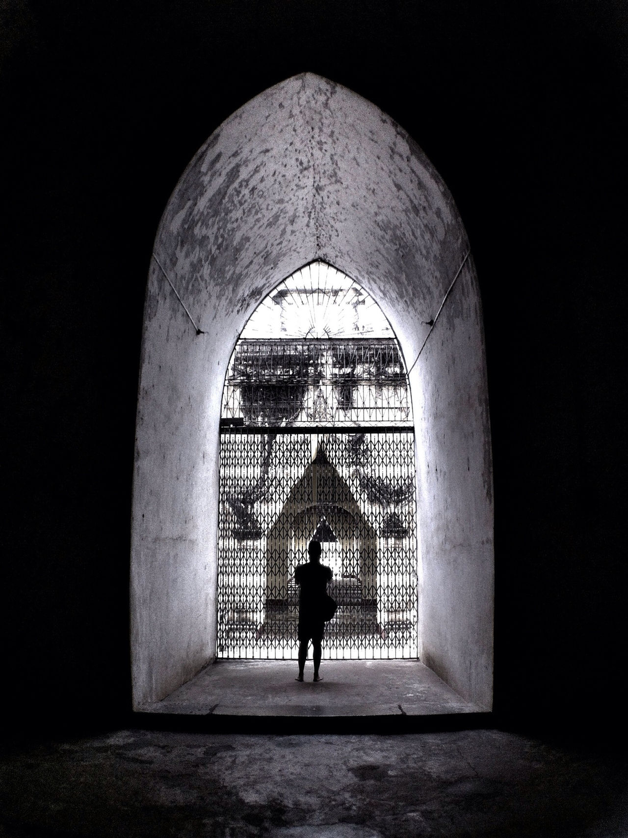 Rear view of man photographing in historical building