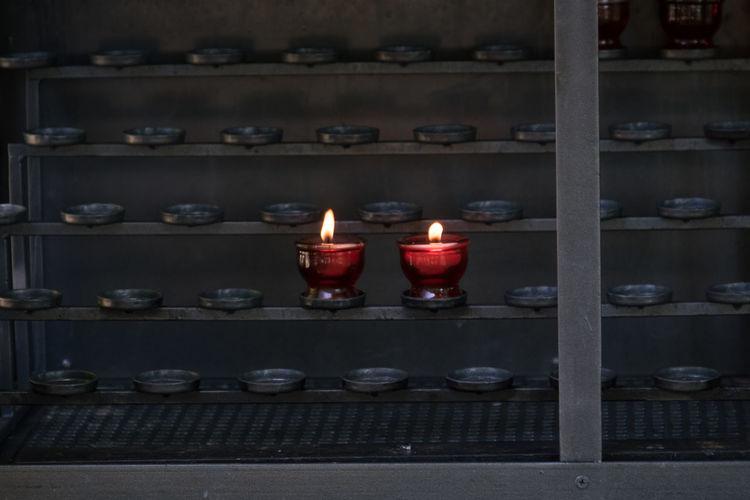 Lit tea light candles on rack