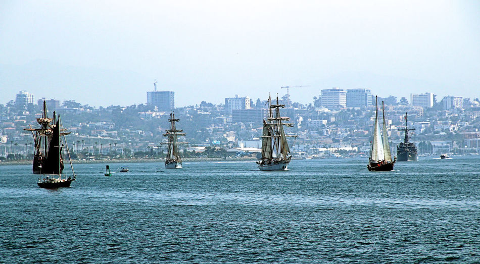 The Tall Ships have left their anchorages and moorings and begin to tack out of the Harbor to rendezvous for the start of the Parade of Sail. Note the U.S. Navy Destroyer escorting the Tall Ships. Tall Ships, Sailing Vessels, Ships, Vessels, Wind Power, Renezvous, Skyline, Bay, Harbor City, Clouds, Parade, Nautical, Naval, Navy, Military, San Diego, California,
