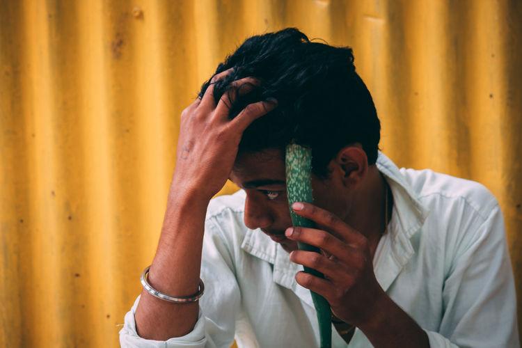 Teenage Boy Holding Aloe Vera Plant While Sitting Against Wall