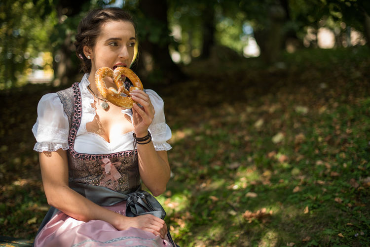 Woman eating pretzel while sitting on field