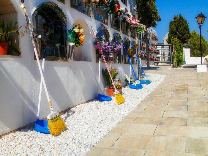 Multi colored flower pots on sidewalk by building