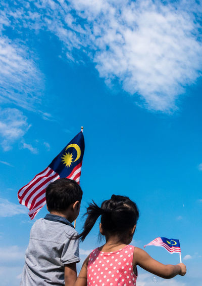 Unknown kids waving Malaysia Flag. Independence day and Merdeka Celebration. Blue sky and copy space. Celebration Children EyeEm Best Shots EyeEm Selects Jalur Gemilang Kids Kuala Lumpur Patriotic Patriotism Blue Sky Boy Childhood Day Flag Girl Independence Day Leisure Activity Lifestyles Malaysia Men Merdeka Multi Colored Outdoors Patriotism People Real People Rear View Sky Striped Togetherness Two People Young Adult
