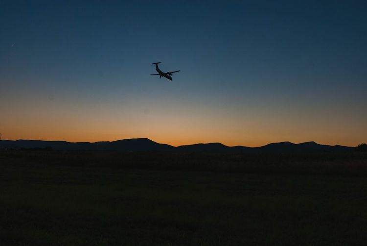 Airplane flying over silhouette landscape against clear sky