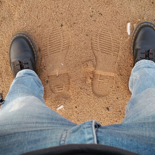 Low Section Of Man Standing By Shoe Prints At Beach