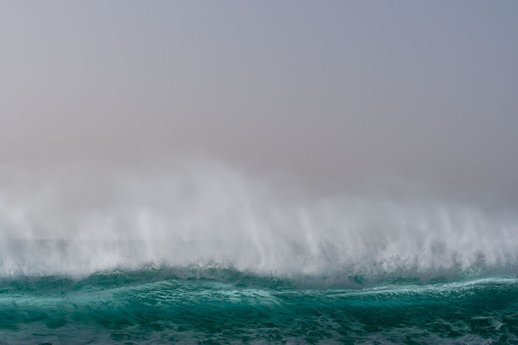Scenic view of sea and big wave  against sky