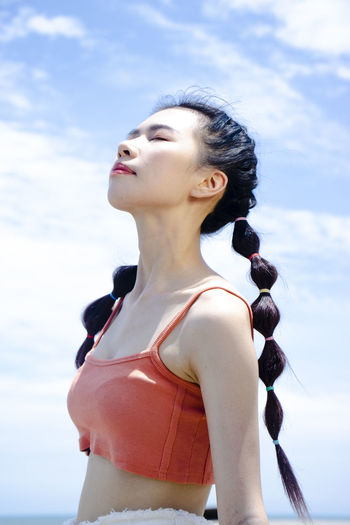 Low section of woman standing against sky