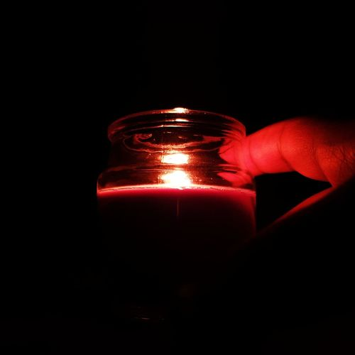 Close-up of hand holding lit candle in the dark