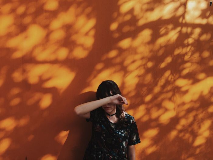 Woman hiding face with hand while standing against orange wall