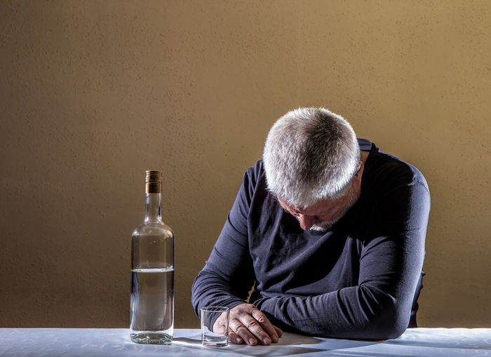 Man having alcohol while sitting at table against brown wall