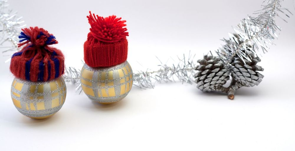 Christmas decoration. Two golden balls with handmade red hats. pine cones and blurred silver ribbon Gold Balloons Red, Beauty In Nature Close-up Day Flower Flower Head Freshness Handmade Indoors  Nature No People Red Studio Shot White Background
