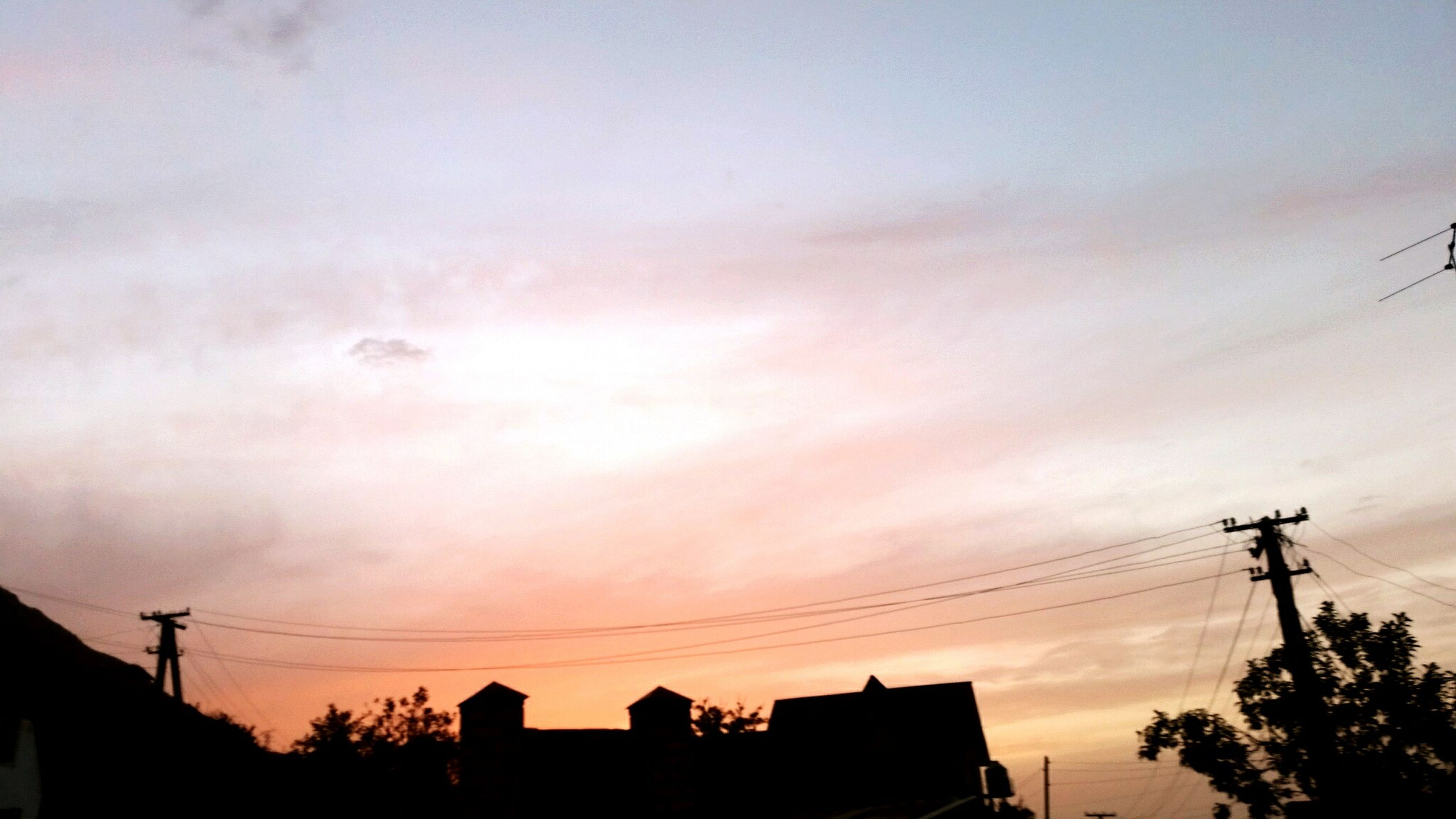 power line, electricity pylon, silhouette, power supply, sunset, electricity, cable, low angle view, sky, connection, building exterior, fuel and power generation, power cable, built structure, technology, architecture, cloud - sky, dusk, house, outdoors