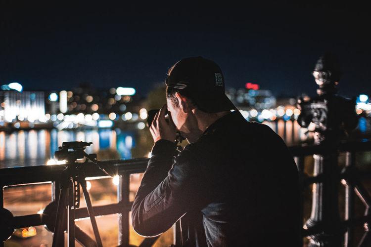 Man photographing illuminated cityscape at night