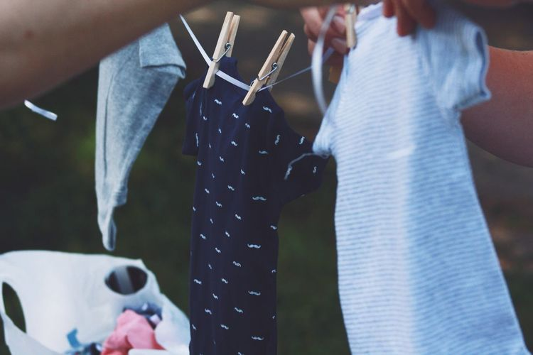 Cropped Image Of Person Arranging Clothes On Rope