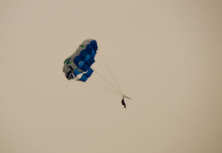 Person parasailing against clear sky