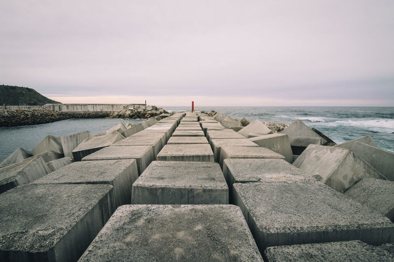 Perspective of concrete cubes seawall at sunset Diminishing Perspective Horizon Over Water Jetty Leading Lighthouse Mood Narrow Nature Ocean Outdoors Perspective Pier Rocks Sea Sea And Sky Seascape Seawall Showcase: February Stone Sunset The Way Forward Vacations Water Water Reflections