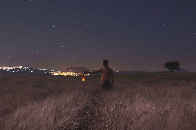 Shirtless Man With Illuminated Lantern Standing On Field