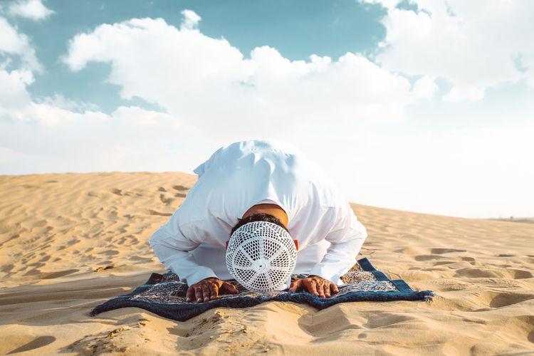 Man sitting on sand dune in desert against sky