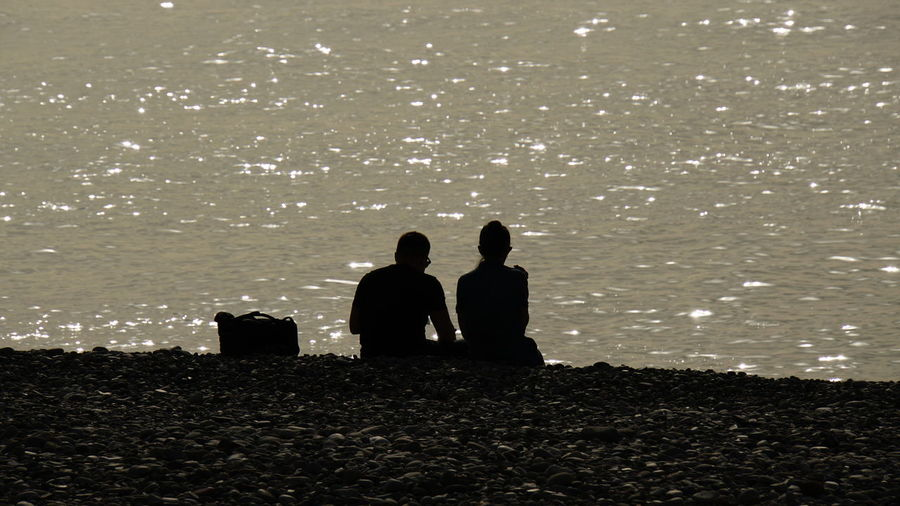 Silhouette couple sitting at beach during sunset