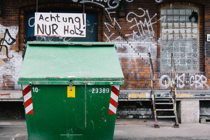 Garbage bin against graffiti on old building