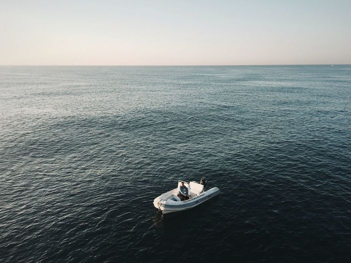 High angle view of man sitting in sea against clear sky
