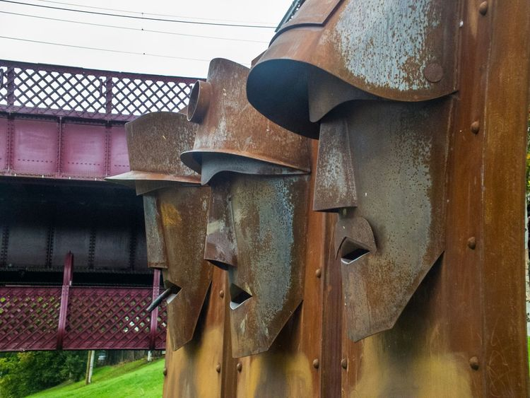Face Sculptures at Summerlee Mining Museum in Coatbridge Scotland Steel Structure  Art Work Metalwork Outside Outdoors Scottish Bridge Rusted Weather Beaten Grass Rough Rivets Welded Memorial No People Horizontal Colour Image Man Made Structure