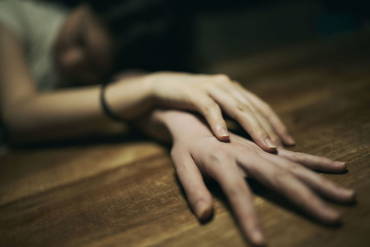 Close-up of woman hand on floor at home