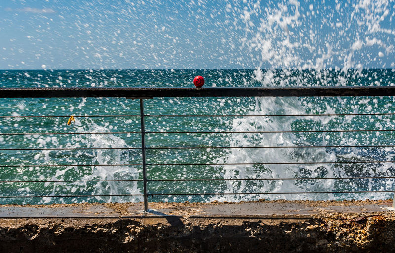 Red Ball On Metal Railing And Sea Wave Splashing In The Background
