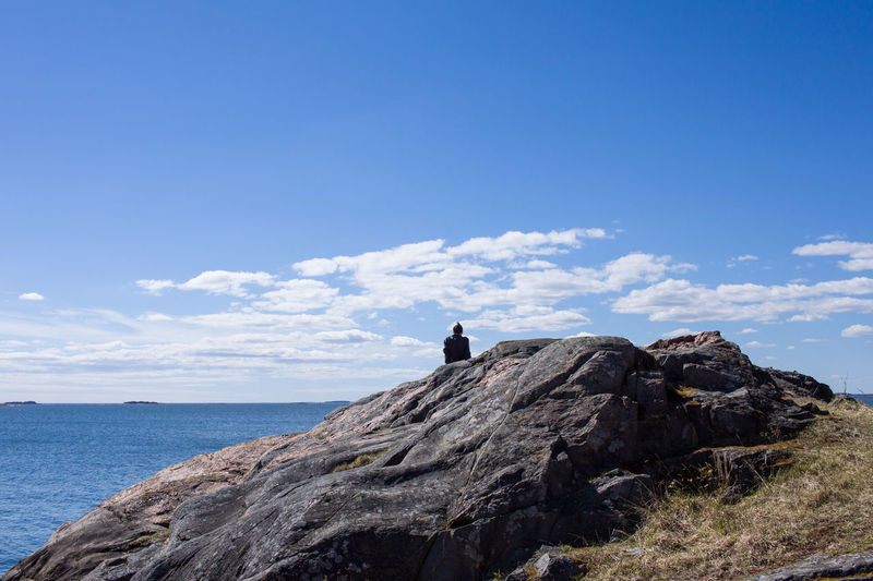 Beauty In Nature Blue Cliff Cloud - Sky Day Horizon Over Water Leisure Activity Lifestyles Mountain Nature One Person Outdoors People Real People Rock - Object Sea Sitting Sky Suomenlinna Tranquility Breathing Space Lost In The Landscape