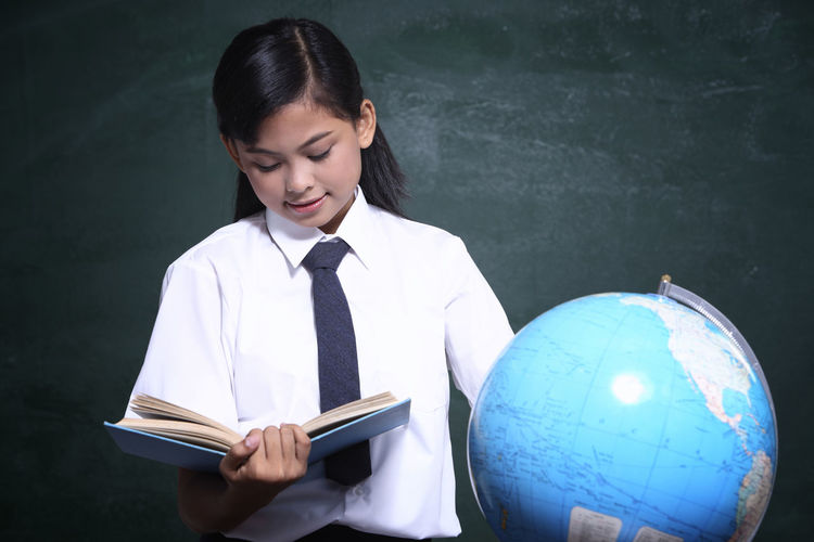 Schoolgirl reading book by globe against blackboard