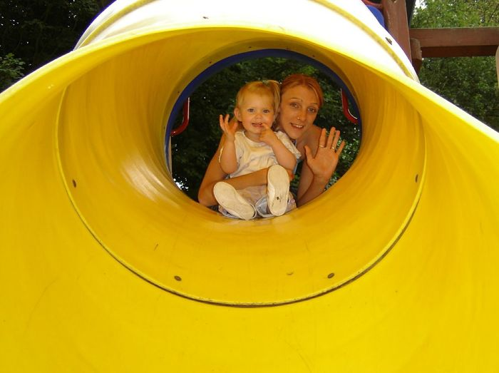 Portrait of happy mother with daughter in slide tunnel