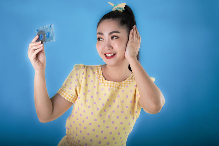 Portrait of smiling young woman standing against blue background