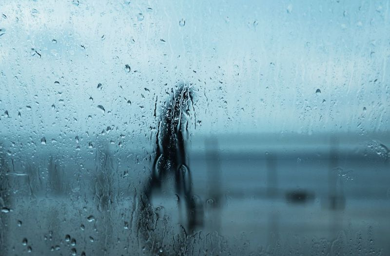Person seen through of wet glass window in rainy season