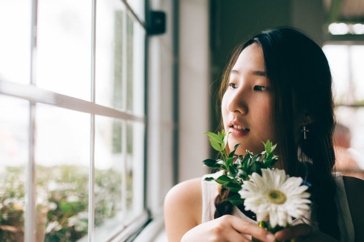 Close-up of woman with flower looking towards window at home