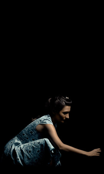 Woman crouched in a blue dress in a dark environment. Black Background Copy Space Woman Crouched Loneliness Forgetfulness Abandoned Guilt Search Yearning Sadness Escape Depression Burden Reach Pressure Endeavor Dissapointment Bitterness Inside Fear Shy Hidden Isolated Darkness