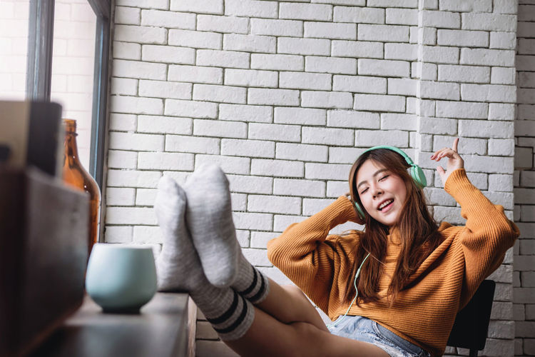 Woman Listening Music While Relaxing At Home