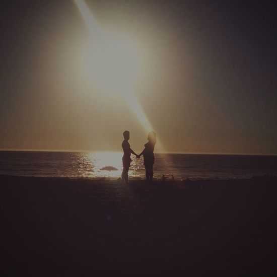 Couple standing holding hands on beach during sunset